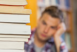 Student studying between piles of books