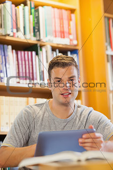 Attractive smiling student using tablet