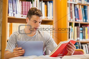 Attractive smiling student using tablet and holding book