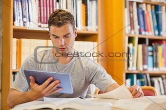 Attractive focused student using tablet and turning page