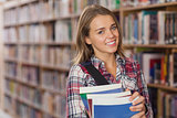 Pretty smiling student holding books