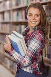 Pretty cheerful student holding books