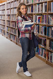 Pretty smiling student looking at camera holding books