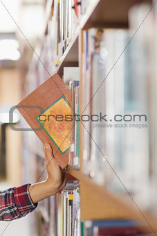 Close up of student taking book out of shelf