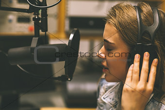 Focused pretty singer recording a song