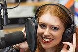 Smiling beautiful singer recording a song