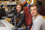 Attractive cheerful radio host interviewing a guest