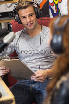 Attractive happy radio host interviewing a guest holding clipboard