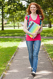 Gorgeous smiling student walking and carrying notebooks