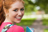 Gorgeous cheerful student holding notebooks looking at camera
