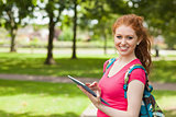 Gorgeous smiling student using tablet