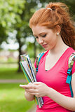 Gorgeous happy student holding notebooks texting