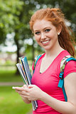 Gorgeous cheerful student holding notebooks texting