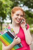 Gorgeous cheerful student holding notebooks phoning