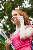 Gorgeous gleeful student holding notebooks phoning