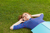 Gorgeous smiling student lying on grass phoning