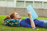 Gorgeous concentrating student lying on grass reading notes
