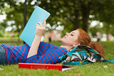 Gorgeous serious student lying on grass reading notes
