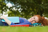 Gorgeous smiling student lying on grass reading notes