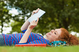 Gorgeous smiling student lying on grass using tablet