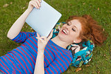 Gorgeous cheerful student lying on grass using tablet