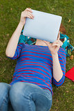 Gorgeous student lying on grass using tablet