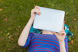 Student lying on grass using tablet
