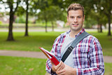 Handsome smiling student carrying folder