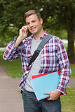 Handsome smiling student standing and phoning
