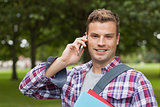 Handsome cheerful student standing and phoning