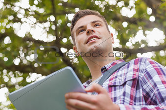 Handsome smiling student using tablet