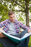 Handsome serious student sitting on grass studying