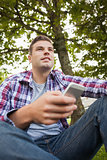 Handsome happy student sitting on grass texting