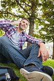 Handsome happy student sitting on grass phoning