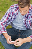 Handsome unsmiling student sitting on grass texting