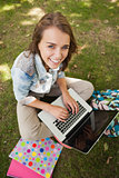 Pretty cheerful student sitting on grass using laptop