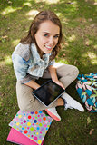 Pretty cheerful student sitting on grass using tablet