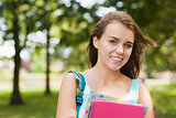 Pretty smiling student holding folder and notebook