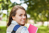 Pretty cheerful student smiling at camera carrying notebook