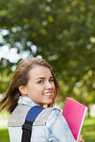 Pretty happy student smiling at camera carrying notebook