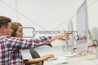 Two students working on computer pointing at it