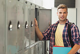 Smiling handsome student standing next to locker