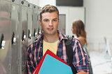Cheerful handsome student standing next to locker
