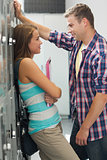 Two students leaning against locker flirting