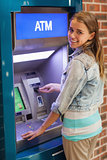 Pretty smiling student withdrawing cash