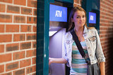 Pretty happy student withdrawing cash smiling at camera