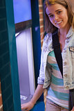 Pretty cheerful student withdrawing cash smiling at camera