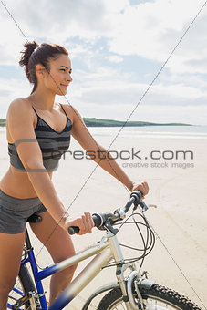 Smiling woman sitting on her bike on the beach