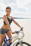 Cute smiling woman sitting on her bike looking at camera
