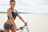 Young woman posing with her bike on beach